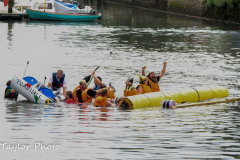 "Kingsbridge - Kingsbridge Fair Week - Raft Race - The ""Faux Fur Vikings"" celebrate sinking ""Toad Hall"""